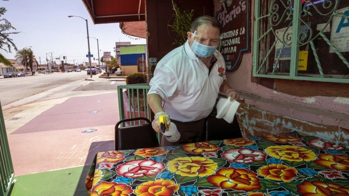 Assistant manager Luis Garcia sanitizes outdoor tables at Gloria's Restaurant in Huntington Park. (Brian van der Brug/Los Angeles Times)
