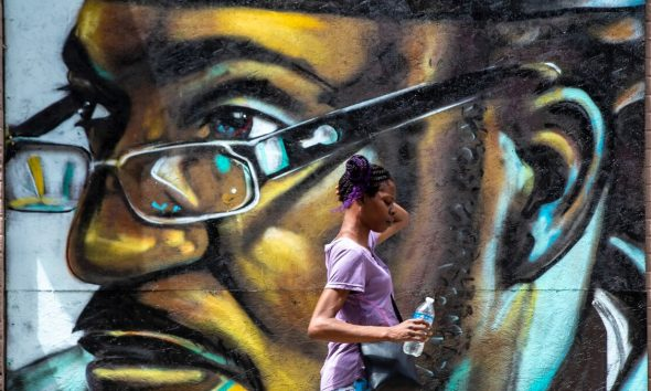 A pedestrian walks past a mural of David McAtee painted by artist Damon Thompson on plywood outside the Limbo Tiki Bar in downtown Louisville, Ky. (Image via Courier Journal)