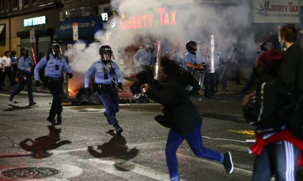 Police charge at a crowd along 52nd Street in West Philadelphia in the early hours of Tuesday, Oct. 27, 2020. (Tim Tai/The Philadelphia Inquirer via AP)